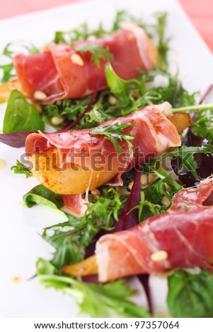 Appetizer with caramelized pears, walnuts and prosciutto - stock photo