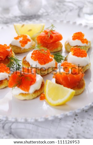 appetizer with caviar and salmon on white plate.
