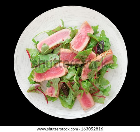 Appetizer with rare fried tuna in plate isolated on black background