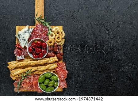 Appetizers board with assorted italian snacks. Gorgonzola cheese, meat, olives, and peppers. Charcuterie and antipasti platter. Top view, copy space Stock photo ©