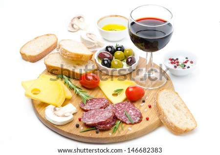 appetizers - salami, cheese, bread, olives, tomatoes and glass of red wine isolated on white
