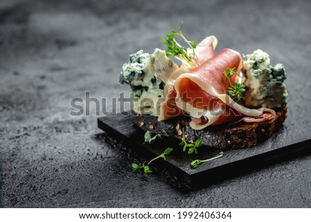 Appetizers. Sandwich with prosciutto and blue cheese. antipasti with red wine. banner, menu recipe place for text, top view. Stock photo ©