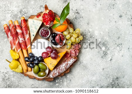 Appetizers table with antipasti snacks. Cheese and meat variety board over grey concrete background. Top view, flat lay, copy space