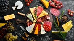 Appetizers table with italian antipasti snacks and wine in glasses. Cheese, wine, salami and prosciutto on a black stone background. Top view. Free space for your text.
