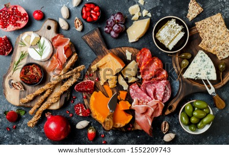 Appetizers table with italian antipasti snacks. Brushetta or authentic traditional spanish tapas set, cheese variety board over black stone background. Top view, flat lay Stock photo ©
