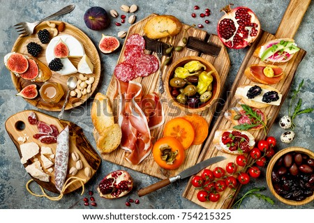 Appetizers table with italian antipasti snacks. Brushetta or authentic traditional spanish tapas set, cheese variety board over grey concrete background. Top view, flat lay Сток-фото ©