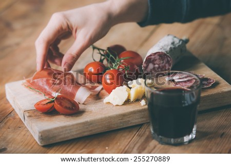 Appetizers - tomato, meat and cheese - on wooden board with  glass of wine. Toned image