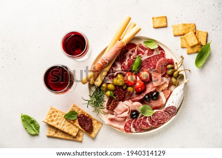 Appetizers with differents antipasti, charcuterie, snacks and red wine on white background. Sausage, ham, tapas, olives and crackers for buffet party. Top view, flat lay Foto stock ©