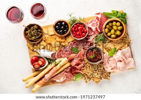 Appetizers with differents antipasti, charcuterie, snacks and red wine on white background. Sausage, ham, tapas, olives and crackers for buffet party. Top view, flat lay Stock photo ©