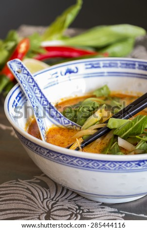 Appetizing Asian Food on White Bowl with Spoon and Chops Sticks on Table