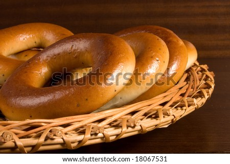 Appetizing bagels on wicker plate at the table