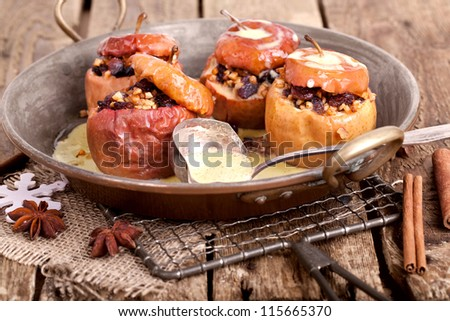 Appetizing baked apples stuffed with raisin and nuts for christmas with vanilla sauce on a old rustic pan on wooden table