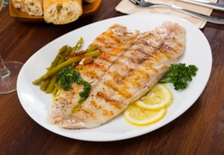 Appetizing baked ocean perch fillet with baked asparagus, sliced lemon and greens
