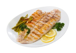 Appetizing baked ocean perch fillet with baked asparagus, sliced lemon and greens. Isolated over white background