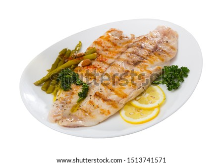 Photo of  Appetizing baked ocean perch fillet with baked asparagus, sliced lemon and greens. Isolated over white background