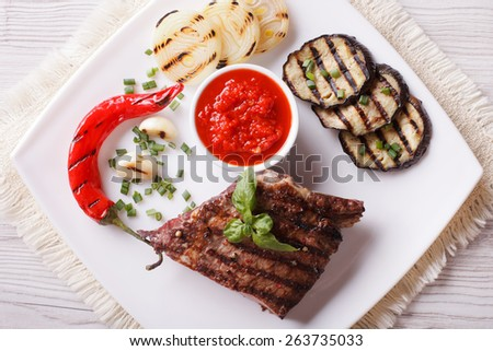 appetizing beef steak, grilled vegetables and sauce on a plate. horizontal view from above