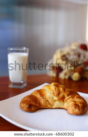 Appetizing croissant on a white plate and glass of milk