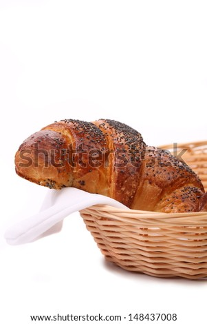 Appetizing croissants with poppy in basket. White background.