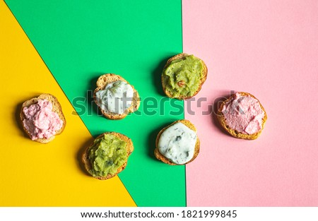 Appetizing crostini or bruschetta with tarama, tzatziki and guacamole sause. Variety of small sandwiches with various toppings on the multicolored background Stok fotoğraf ©
