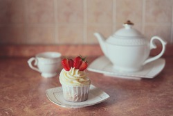 Appetizing cupcake with white cream decorated with fresh strawberries on the table, accompanied by a white teapot and cup.