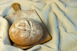 Appetizing freshly baked bread has just been put on the table. The image also features a background of flour-coated cutting board and drapery. Homemade bread, bakery.
