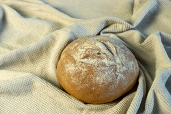 Appetizing freshly baked bread has just been put on the table. The image also features a background of drapery. Homemade bread, bakery.