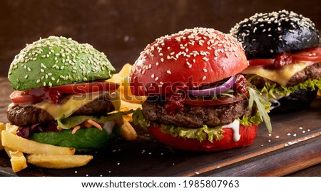 Appetizing hamburgers with colorful buns and meat cutlets served on table with French fries Stock photo ©