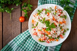 Appetizing healthy rice with vegetables in white plate on a wooden background. Selective focus. Top view.