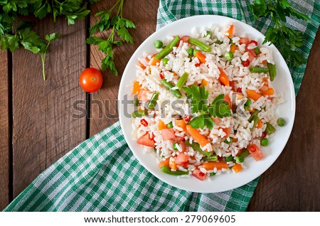 Shutterstock Appetizing healthy rice with vegetables in white plate on a wooden background. Selective focus. Top view.