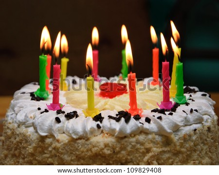 appetizing holiday cake with the light colorful candles
