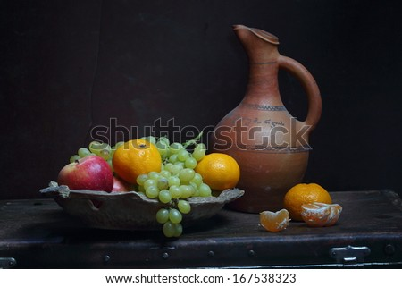 Appetizing juicy green grapes and fragrant red sweet apples and ripe bright tasty tangerines in a copper plate and a clay jug