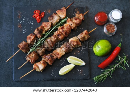 Appetizing kebab with spices, chili and lime. Fragrant pork skewers on a stone board. #1287442840