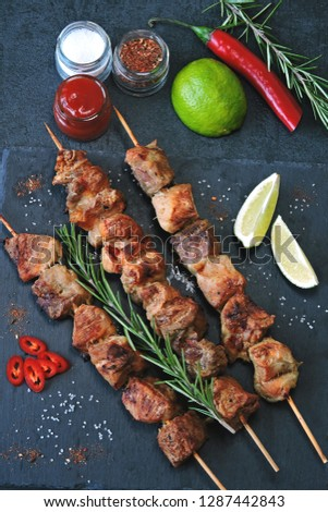 Appetizing kebab with spices, chili and lime. Fragrant pork skewers on a stone board. #1287442843