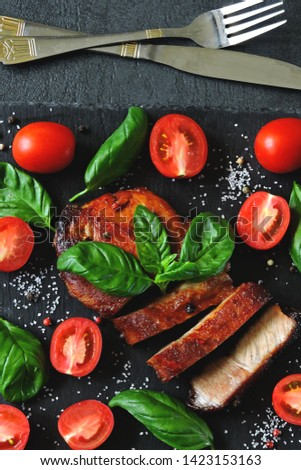 Appetizing meat steak with tomatoes and basil on a stone board. Balanced nutrition concept. Paleo diet. Pegan Diet. #1423153163