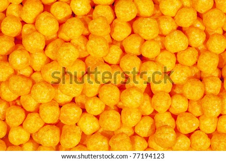 Appetizing orange puffy cheese balls, snack background