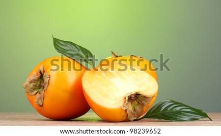 Appetizing persimmons on wooden table on green background