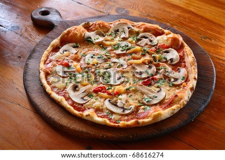 Appetizing pizza with mushrooms on a wooden tray
