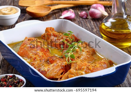 appetizing Rabbit Cooked in mustard cream sauce with spices in gratin dish on wooden table with bottle of olive oil and garlic on background, classic french recipe, view from above, close-up