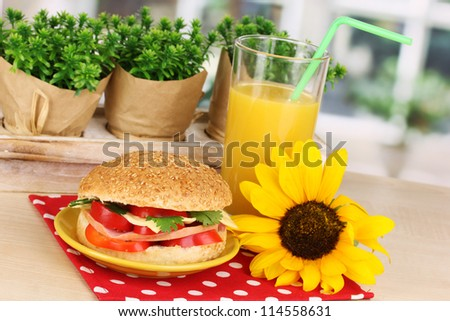 Appetizing sandwich on color plate on wooden table on window background