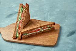 Appetizing sandwich with salmon, cucumber, tomato and white sauce on a board on a gray background