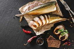 Appetizing smoked fish with spices, cutlery, pepper and bread on craft paper over dark stone background. Sandwich with smoked mackerel. Mediterranean food, herring fish, seafood, top view