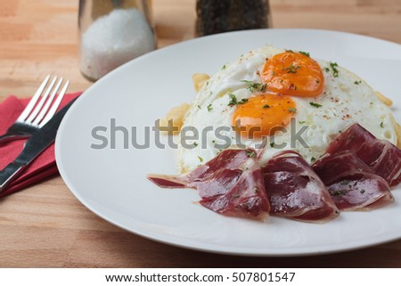 Shutterstock Appetizing Spanish Iberian cured ham with fried egg and chips on wooden plate on white background.