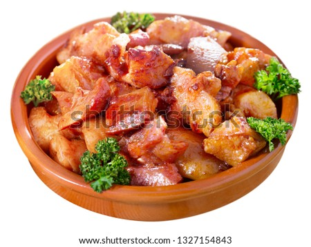 Appetizing stewed chopped pork snouts (Morro de cerdo) decorated with fresh parsley. Isolated over white background