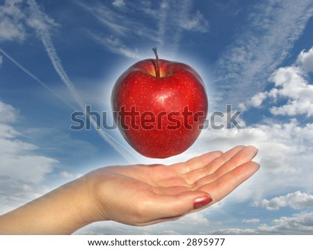 Apple above a hand on a sky background