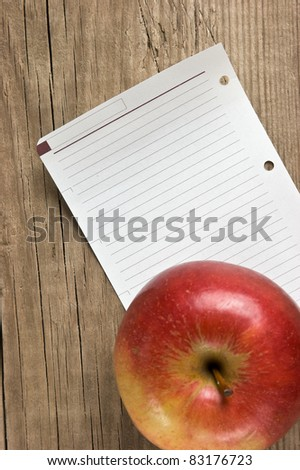 apple and a note  on a wooden background