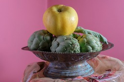 Apple and artichokes still life. Pink background. Metal antique bowl. Pictorial.