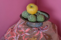 Apple and artichokes still life. Pink background. Metal antique bowl. Pictorial design.