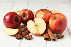 Apple and cinnamon on wooden background, close up