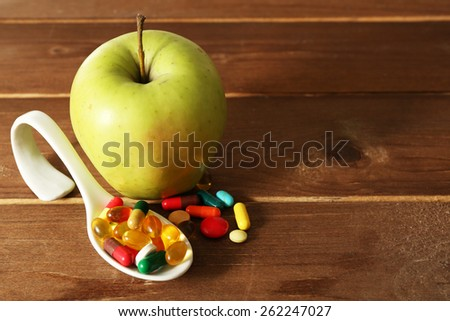 Apple and colorful pills, on wooden background