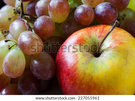 Apple and grapes closeup. Fruit set: red apple and and purple grape.